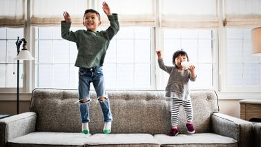 brother and sister jumping on the couch playfully