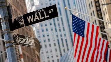 Wall Street and Broad Street signs with an American flag in the background