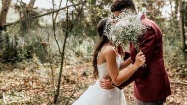 bride and groom kissing behind bouquet