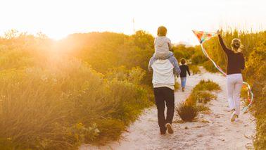 family walking on beach with kite