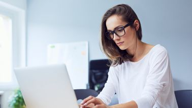 A woman with glasses working on laptop