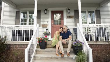 Couple sitting on front porch steps.
