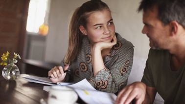 Dad at a table asking his daughter financial questions before they decide on a college