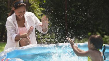 A woman plays with her child in a kiddie pool
