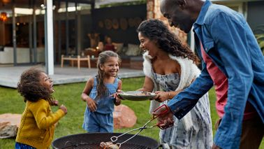 family cooking around outdoor grill for backyard barbecue