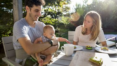 Parents eating outside discussing financial moves for their baby.