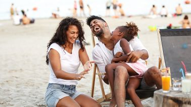mother, father and daughter laughing on beach