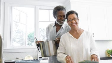Couple cooking in their kitchen and discussing the difference between a pension and an annuity.