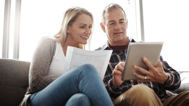 Couple looking at a tablet researching whether an annuity is an investment or an insurance policy.