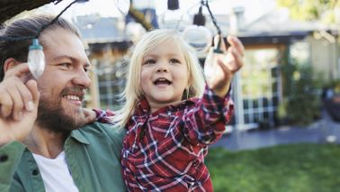 Dad playing with a string of lights with his daughter as he thinks about how life insurance works.