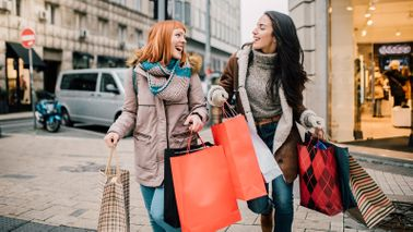 Two women carrying shopping bags trying to prevent holiday overspending.