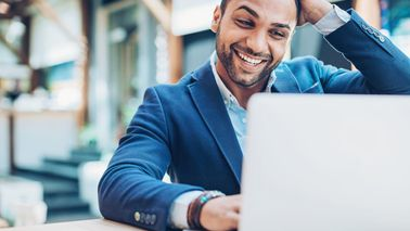Man smiling while looking at laptop
