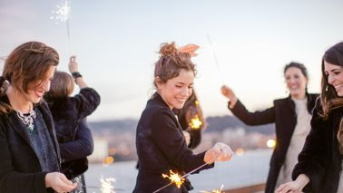 A group of friends waving sparklers around at a party.