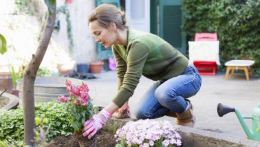 Woman planting flowers for April Buy