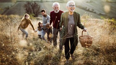 Senior woman with family climbing hill in dream retirement