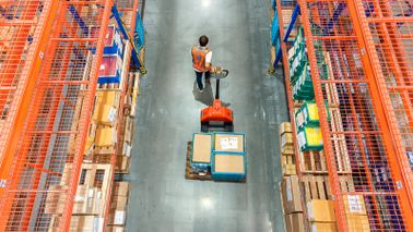 warehouse worker moving items with pallet jack