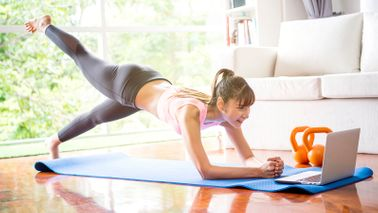 woman doing yoga with online app on laptop