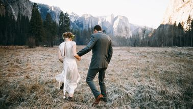 newlyweds walking toward mountains