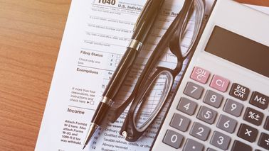 Tax form, glasses and calculator