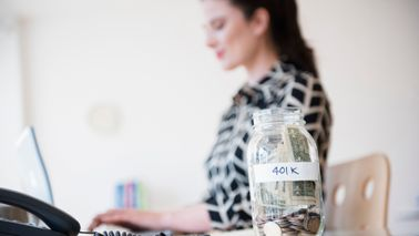 401k money jar on desk of young businesswoman