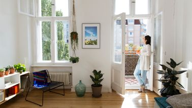 Woman at home standing at balcony door