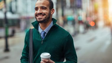 Businessman walking down the street with coffee