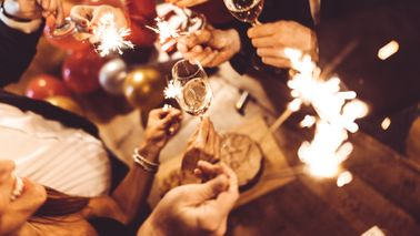 Friends celebrating with champagne and sparklers.