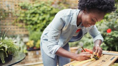 Young woman measures wood for renovation project.