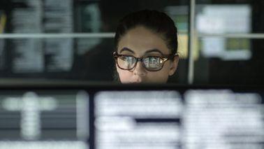 A market analyst studies data on a computer screen