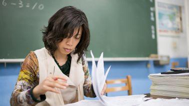 A school teacher grading papers at her desk