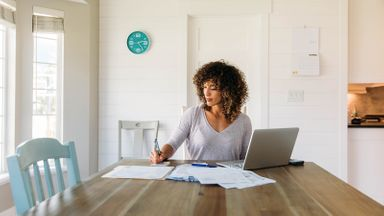 Woman sitting at table doing her finances