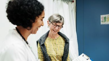 A female doctor speaks with an elderly patient at her medical practice