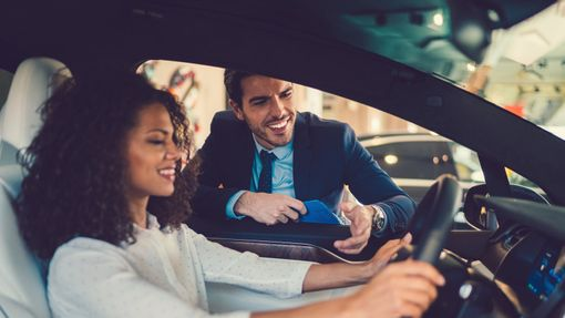 a young woman car shopping and considering a 7-year auto loan